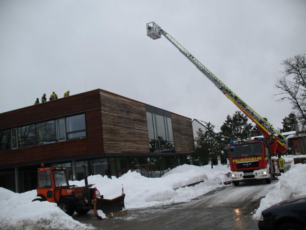 Mehrere Freiwillige Feuerwehren sind im Einsatz, um das Dach der Schule vom Schnee zu befreien. (Foto: Erhard)